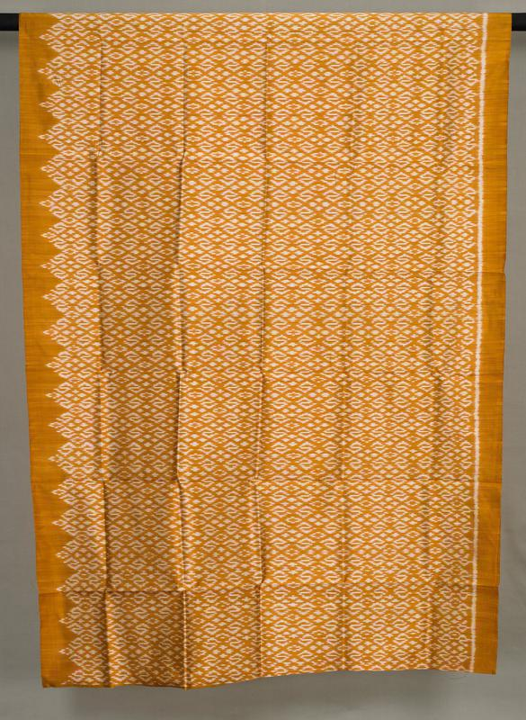 orange with white ikat-like designs; white line at one side; design terminating in zigzags at opposite side; scattered pink threads in design
