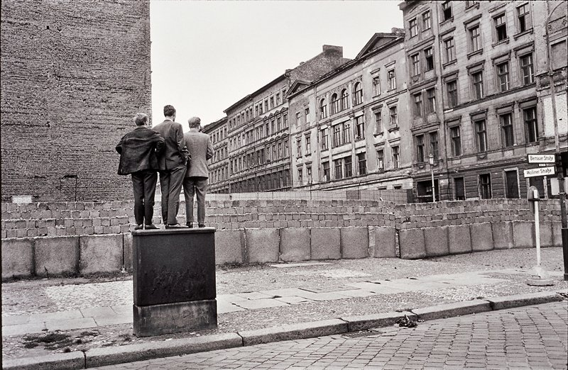 three men standing together on a metal box looking over the Berlin wall on Wollinerstrasse