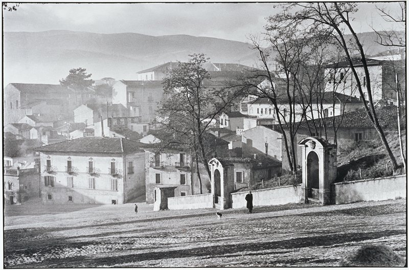 city view with hills in the background; main feature is a stone wall with tall arched niches