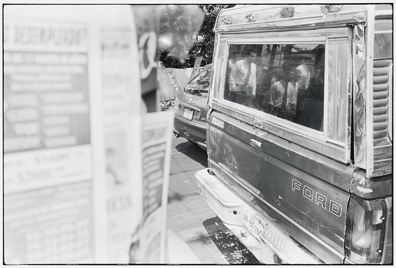 back of Ford pickup truck with topper at right; men wearing white shirts and ties reflected in topper's window; blurry posters at left