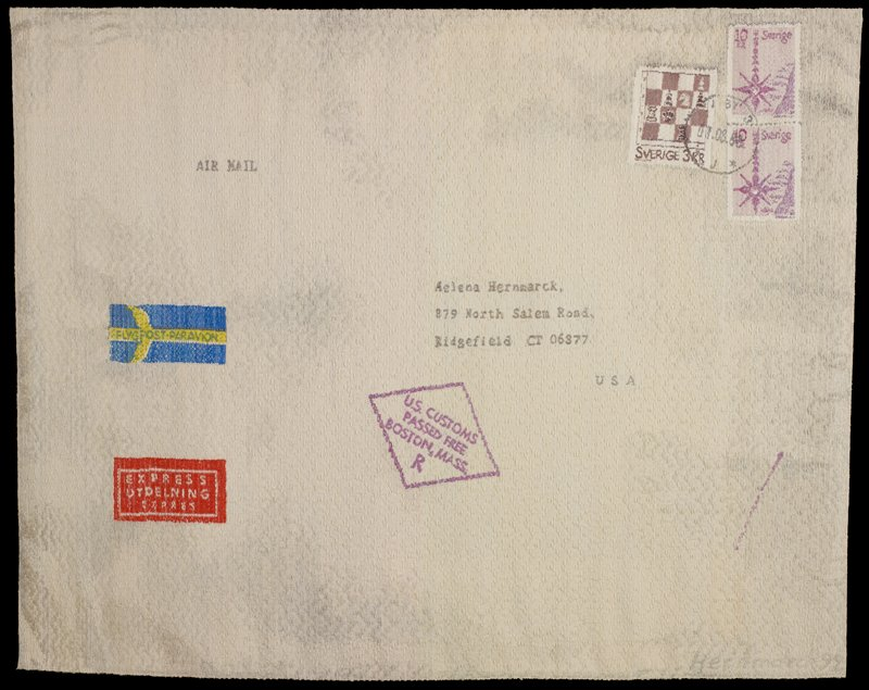grey and cream ground; image of an oversized envelope with three cancelled stamps in URC, purple U.S. Customs stamp below address, red and white sticker, and yellow and blue airmail sticker at left; white heading band on back
