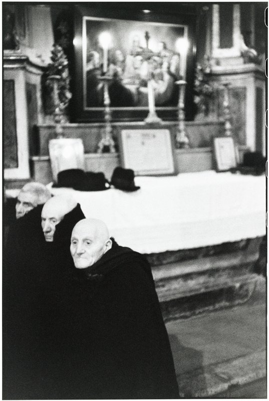 three bald men wrapped in black robes stand before an alter with their hats on it