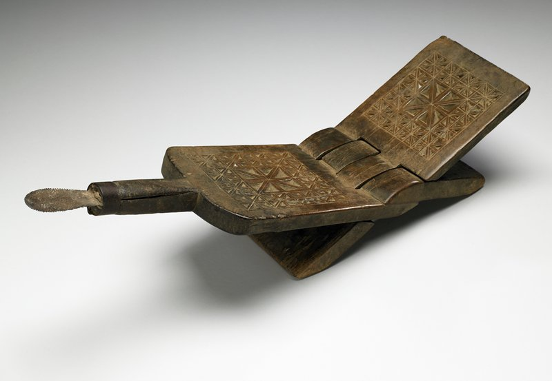 folding design with hinge in center--can be unfolded into X shape or folded flat into paddle shape; saddle-like, when unfolded, with handle with ovoid-shaped serrated metal spatula at end; each side of seat carved with star-asterisk designs in regular geometric grid; medium patina
