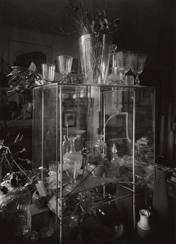 glass shelf with glassware; some dried plants