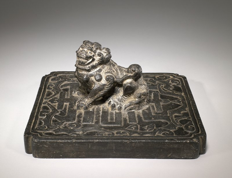 black-brown stone; square bottom plate with indented corners, carved in low relief on top with bats and geometric symbol (Chinese character?); three dimensional Fo dog on top, looking toward PL
