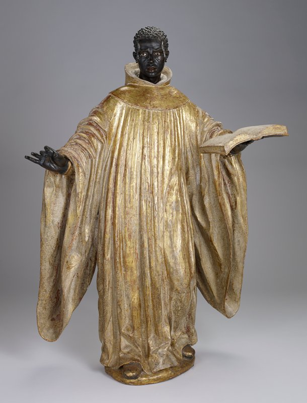 standing black figure with short curly black hair, wearing a gold robe and gold shoes; man has arms outstretched, holding open book in PL hand