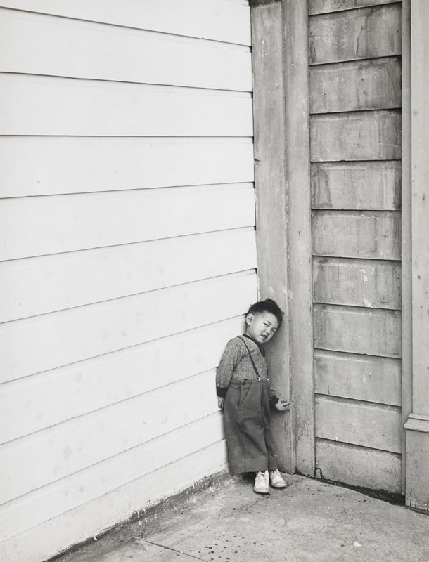 little boy standing in a corner with white paneling on left wall and small panel with horizontal planks on right wall; child wears long-sleeved shirt, pants with suspenders and white shoes