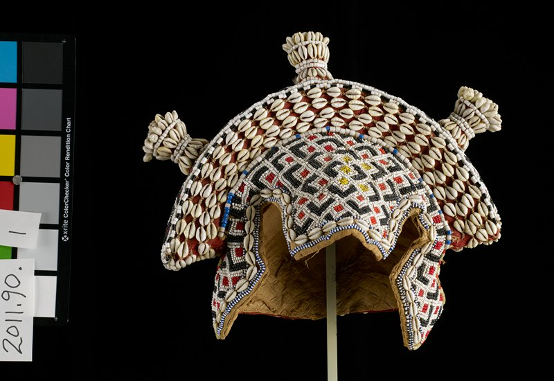 beaded crown; shells and small and large beads; three projections along top; front and sides beaded; center back of hat is plain except along edges; top section with knobs is an added three-dimensional section; lined; beads are red, white, black, yellow and olive