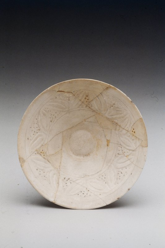 Bowl, carved, and pierced design on white ground under transparent glaze.
