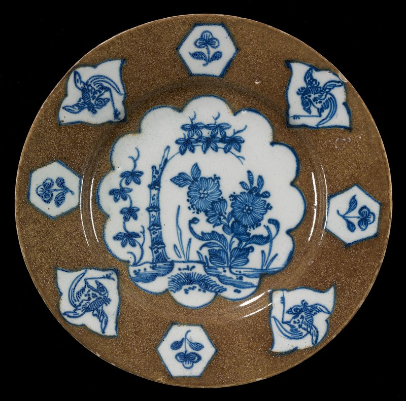 brown ground; white on bottom; central scalloped cartouche and hexagonal cartouches alternating with organic cartouches in blue and white; flowers and bamboo stalk at center; flowers alternating with birds around rim
