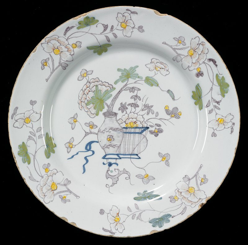 plate decorated with chinoiserie still life of tall jar with flowering branch; striped exterior containing flower and vines at lower bowl; flowers with vines around rim; green leaves, blue ribbons, orange flower veins with yellow centers