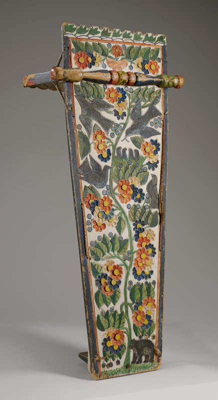 "back panel carved in low relief and decorated with four blue birds, four small birds in a nest, tall twining flowering vine; small bear in LRC; brightly-colored pigments; top ""handle"" carved with twisted design and painted in yellow and red; footboard painted with radiating U shapes"