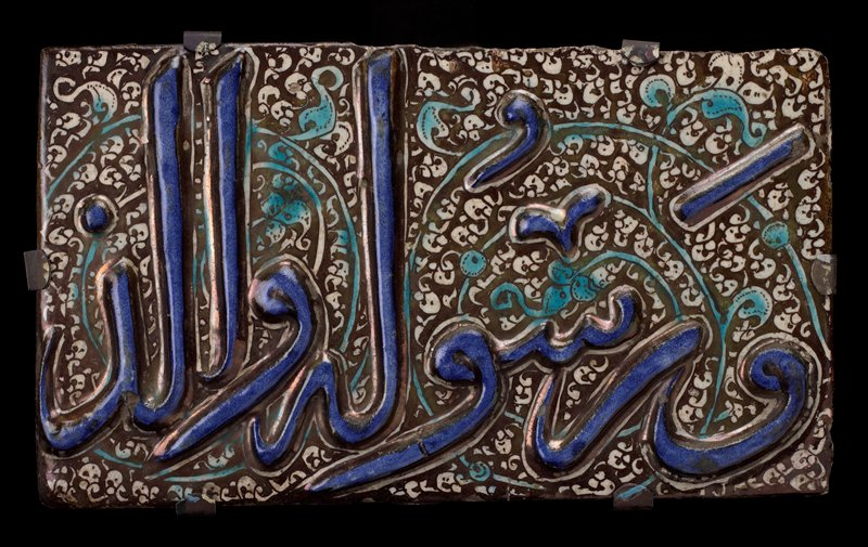 Tile, Sultanabad, pottery, raised blue inscription on black and white floral background.