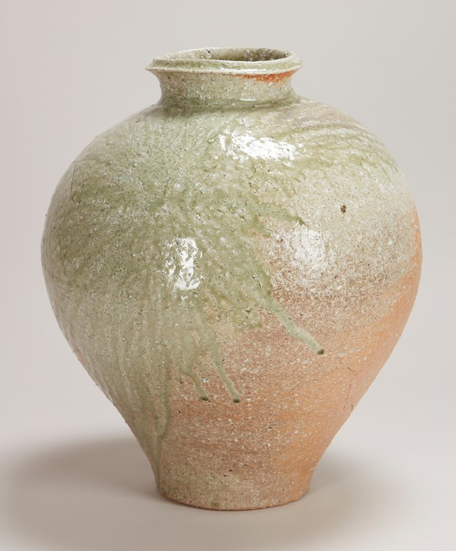 Large rounded form with small diameter base and neck; green glaze covers side and shoulders of form and drips towards opposite side, which shows two circular forms impressed upon the surface.