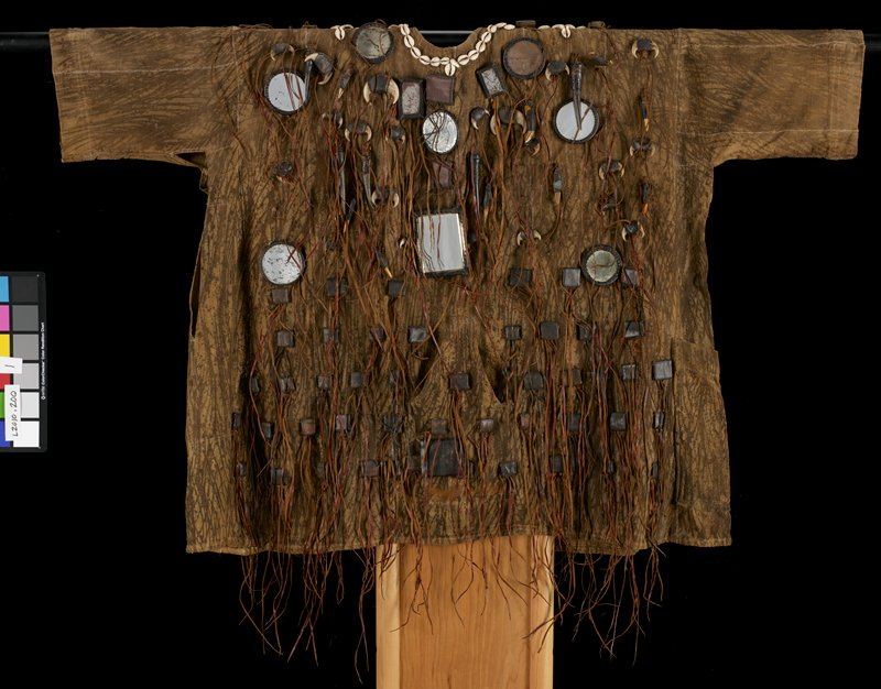 tan with brown painted streaks forming camouflage design; leather tassels overall on front and back; leather-covered mainly square and rectangular button-like embellishments overall; zipper on front top; cowrie shells around neckline; animal teeth and claws hanging from some leather fringes; scattered rectangular and circular leather-backed mirrors
