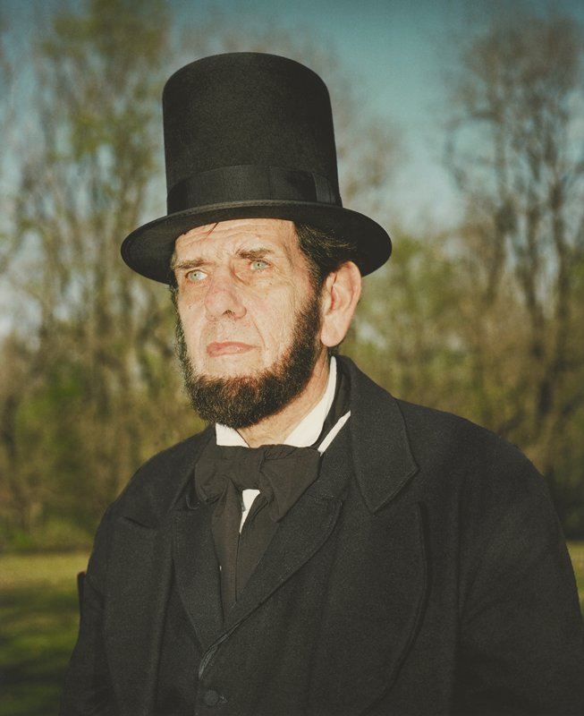 three-quarter portrait from chest up of blue-eyed, bearded man dressed as President Lincoln; blurry trees and blue sky in distance; framed behind glass in black wood frame; one of a set of 18 photographs to be displayed together