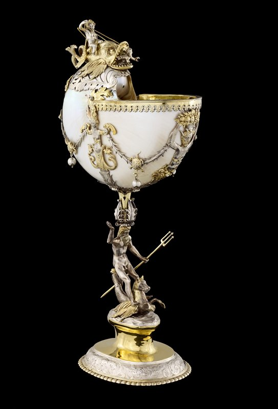 ovoid foot with beaded edge and silver rim decorated with scrolls and flowers; long stem with silver and gilt figure of Neptune with long hair and beard, holding a trident, riding a hippocamp; Neptune wears elaborate scrolled crown; nautilus shell forms cup, decorated with gilt and silver mountings with swags, a grotesque face, two caryatids, and a satyr, with two crabs and two turtles holding decorative silver ball pendants; topped with Jonah (?) emerging from the whale's mouth; whale ridden by Cupid (?), holding gold reigns