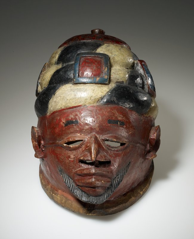helmet in the form of a man's head, with a small triangular face; hooked nose; openings under nose and at eyes; stylized ears; short, pointed black beard; high rectangular black eyebrows; looped, beehive-like headgear with five buckle-like elements in blue, black, white and red; beanie-like top of headgear with knob; rather bright polychromy
