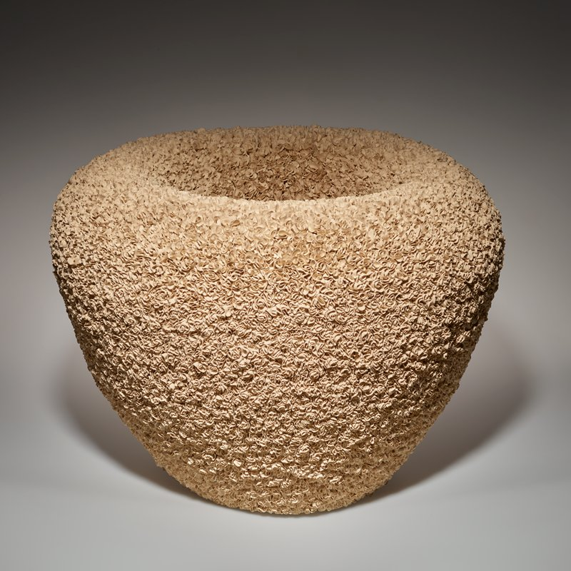 thick-walled vessel, flaring outward from base to wide shoulder, continuously curving inward toward inner walls; vessel covered overall, inner and outer walls, with small twisted and rolled elements with irregular edges, resembling flower petals; light beige color