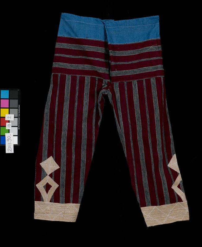 maroon and grey striped fabric; blue panel at top; tan machine embroidery on outside of leg near bottom and wide band around bottom edge; diamonds and triangles; drawstring at waist