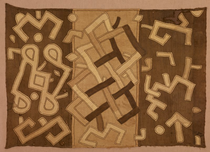 three sections--two with dark brown ground flanked central section with medium brown ground; outer sections have light brown geometric shaped appliqués in random patterns; central section has geometric appliqués in dark, medium and light brown with primarily rectangular motifs; received mounted