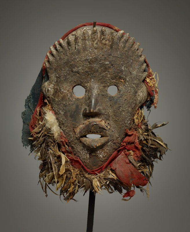 human face mask with pointed chin; points around top front of head forming stylized hair; round eye openings; red and blue cloth (some printed cotton) around sides of face and chin; plant fibers and fragments of feathers around chin; face encrusted--particularly upper lip; received attached to black metal mount