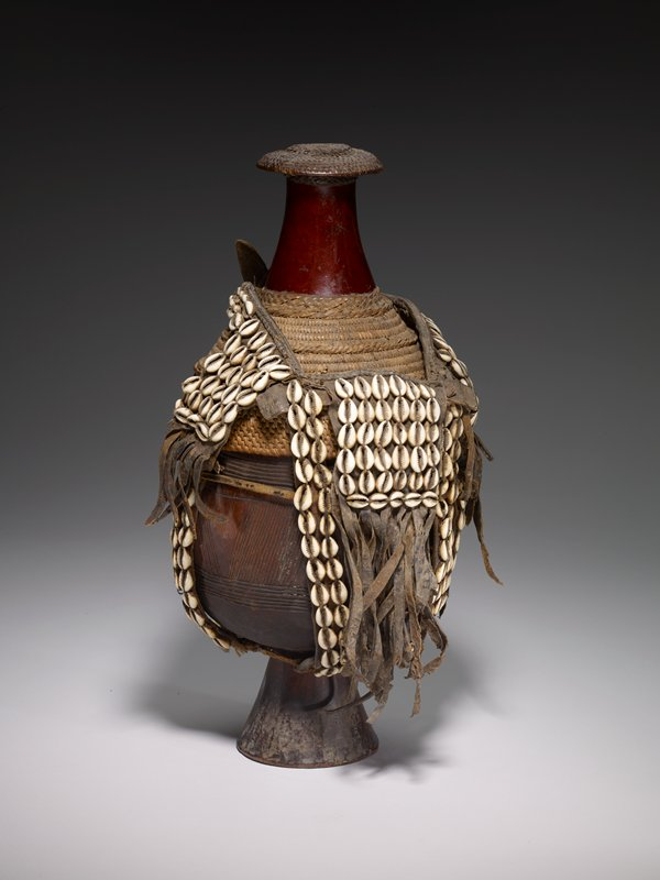 wood vessel with rounded bottom sits on conical base; carved with horizontal bands and wide central band with diagonal incised lines; cover may be part of a gourd, with braided and woven bands of plant fibers around bottom and top forming knob; elaborate straps attached to body of vessel, made of animal hide, with fringe in some areas, decorated with braided plant fibers and cowrie shells