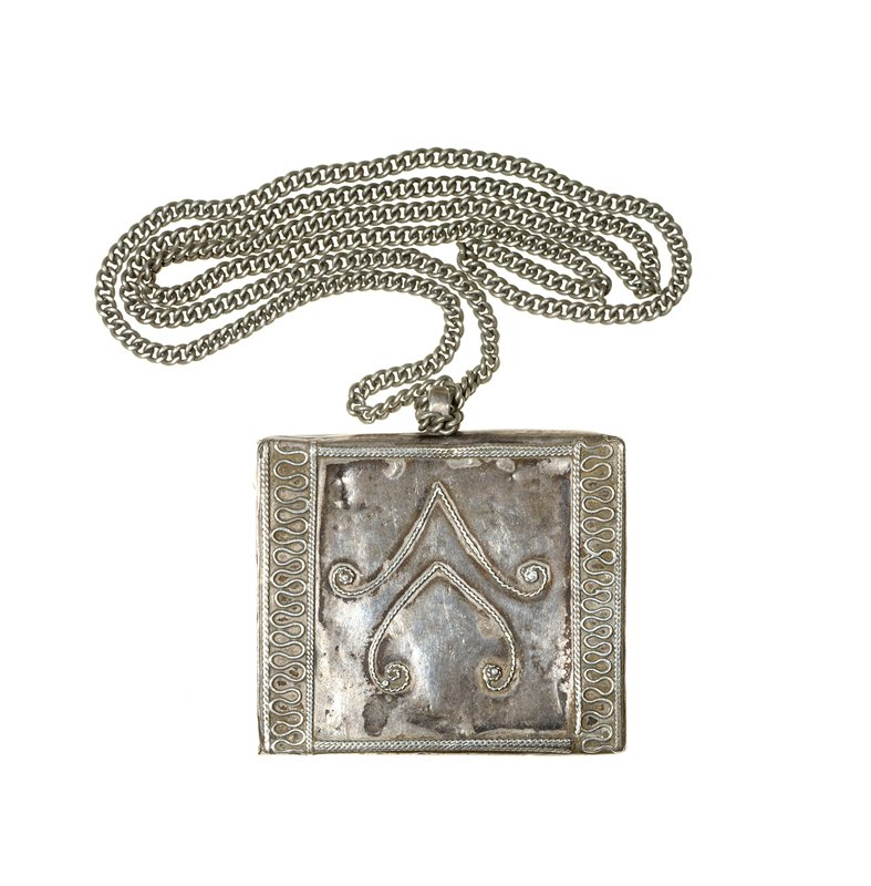 square pendant; three-dimensional, with design on front made of applied twisted and untwisted silver wire; two central chevrons with spiral ends; edges decorated with wavy vertical lines bordered with twisted wire strands; core of pendant may be wood; chain without clasp or closure, attached to pendant by looping (chains for .42 and .44 received separated from pendants)