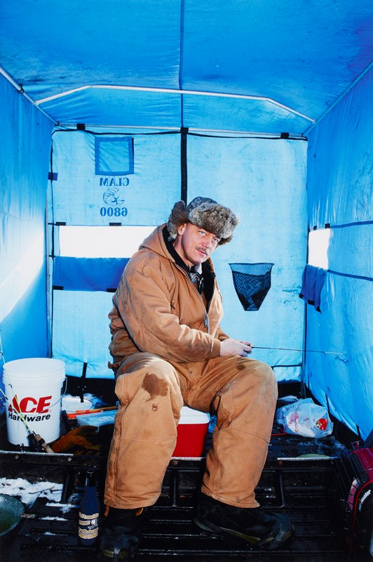 LON139185; caption: USA. Minnesota. Minneapolis. Winter Games. Ice Fishing. Mitch Madsen. 2012.; color image of man sitting inside blue tarp ice fishing house; various fishing gear strewn about; man wears tan overalls and fur hat