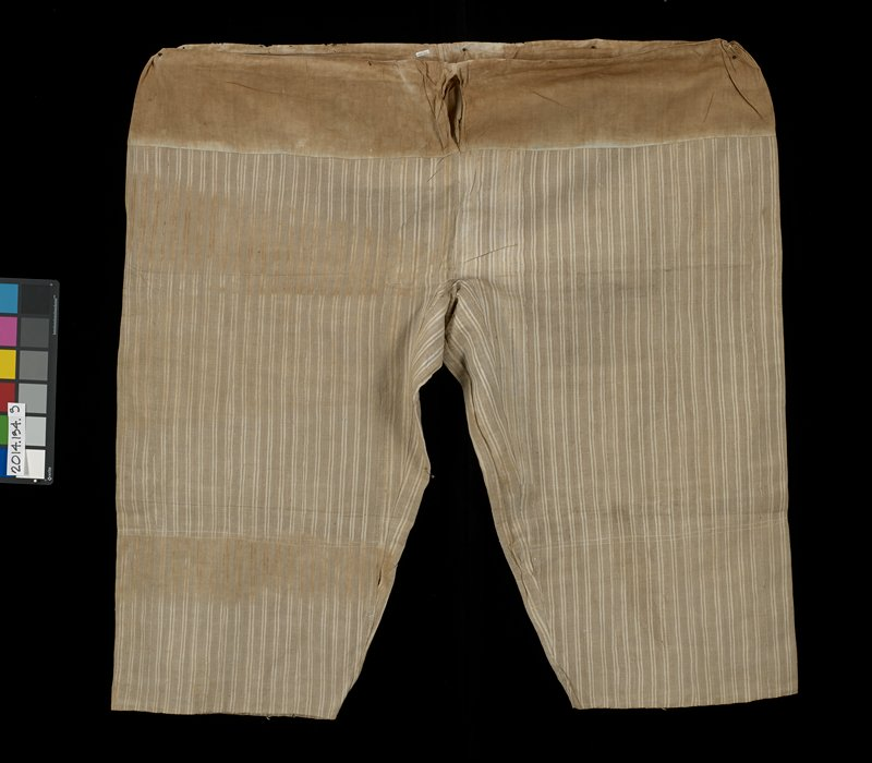 vertically striped tan and white pants with natural brown waist; blue inner lining at cuffs; elastic-like waist