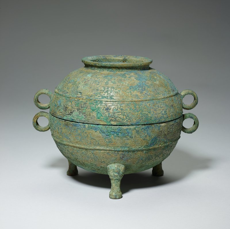 This ting represents the Huai style at its extreme point in the matter of the vessel shape. The tradition that in this style the body of the Ting is big and bulky in proportion to the extremely short, thin legs, is here carried to the ultimate degree. The high lid, its ring-shaped top capable of serving as a foot if the lid is inverted, is fully spherical in shape. The legs are very small and thin and display a t'ao-t'ieh with spiral horns on their upper parts. (The t'ao-t'ieh, all but extinct during Middle Chou, reappeared in the Huai Style Period). Dissolved dragon rigid ring handles are adorned with a row of cowries bordered by rope-patterned bands. On the top of the lid, a loosely twined cord pattern encloses a quartefoil with its central disk filled with granulation. Patina blue-green.