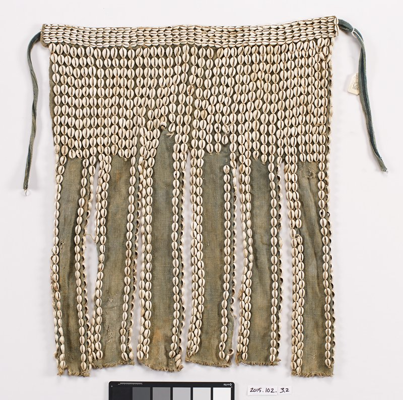 "six panel skirt covered with cowrie shells; panels joined at top for approximately 8"" below waist band; below that not joined; two rows shells edge each side of each panel; base fabric greenish tan; waist band 2"" wide with 4 rows of shells along length; ties attached at ends"