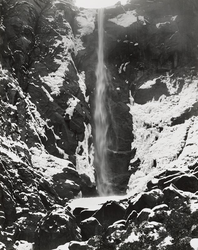 narrow waterfall; snow on rocks surrounding falls