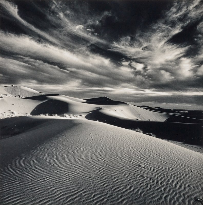 sand dunes with some scrubby plants; striated clouds
