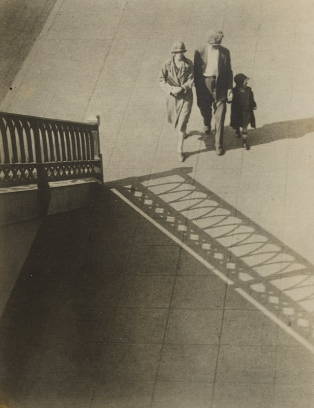 walking woman, man and child, who holds man's hand, with a railing with cross and arch designs at left casting a shadow on sidewalk in front of people
