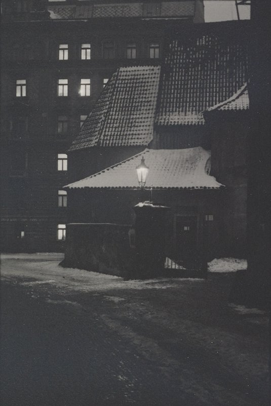 street scene at night with street light and lights in windows in background; snow on tile roofs at center