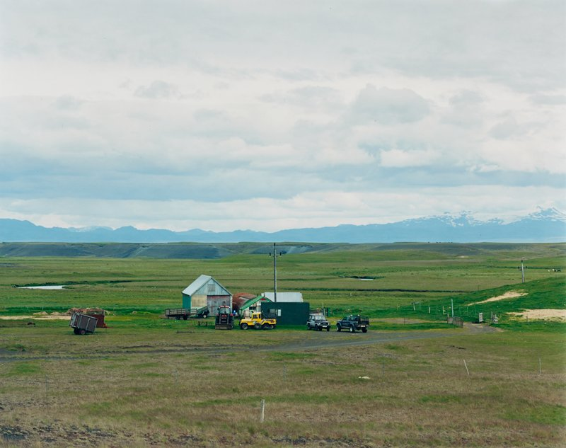farmland with cluster of outbuildings at center with two pickups, several small trailers and two pieces of construction equipment at center; snow-covered mountains in background