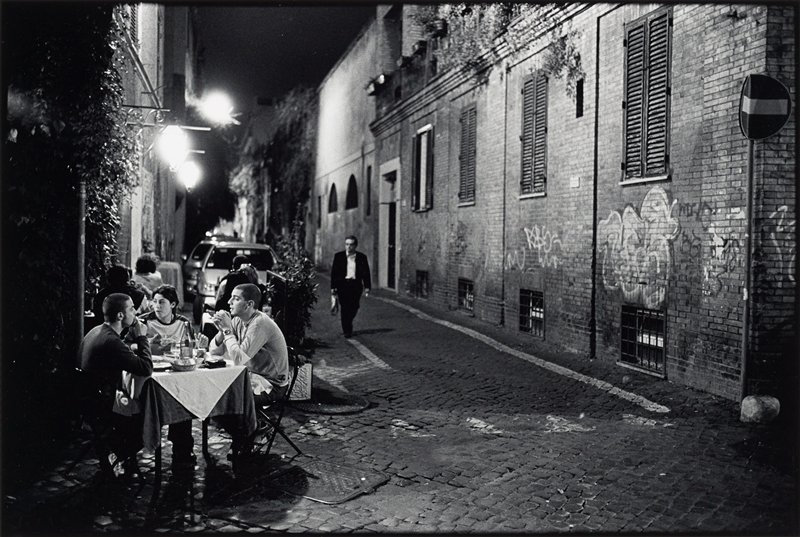 young woman and two young men seated at a small dining table on cobblestone street in front of restaurant at night, LLC; man walking down street at center; wall of brick building with closed shutters and graffiti at right