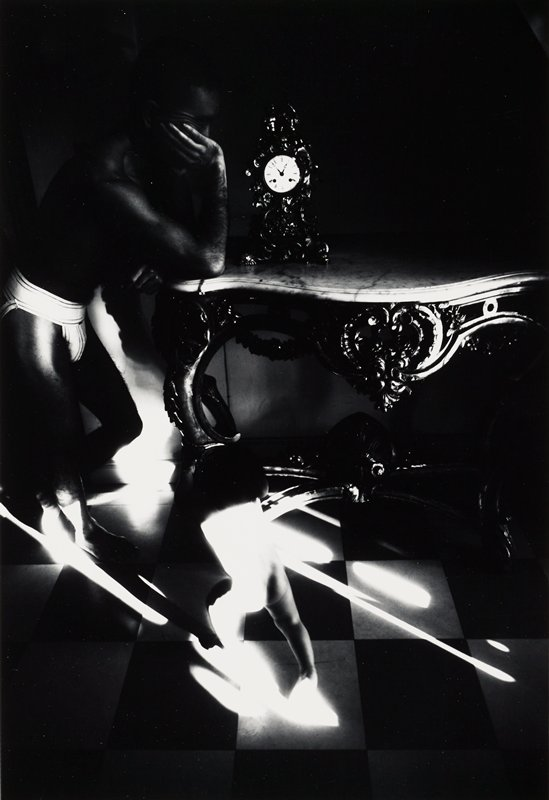 surreal image; man at left, wearing athletic support, leaning his PR elbow on a marble-topped table with an elaborate clock on tabletop; nude baby, seen from back, at bottom center; bright diagonal light streaks at bottom half