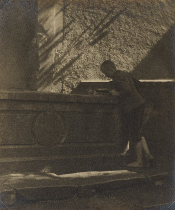 barefoot boy wearing knickers looking over a concrete ledge
