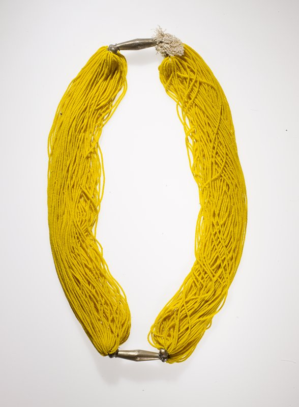 many strands of small yellow beads attached at two opposite ends with large metal clasps; one dark blue bead