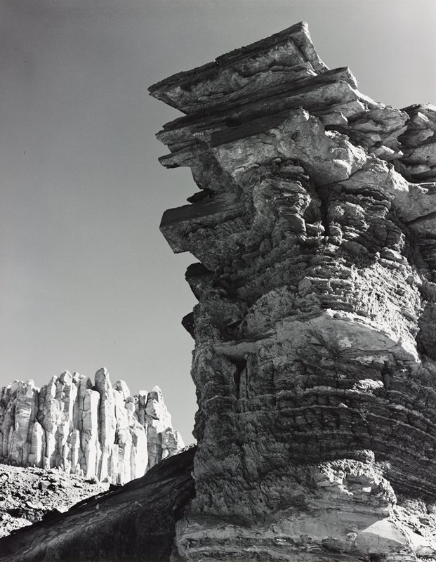 tall, jagged rock formation at right, with horizontal striations and squared-off rock plates; vertical rock formations at left in LLQ; clear sky