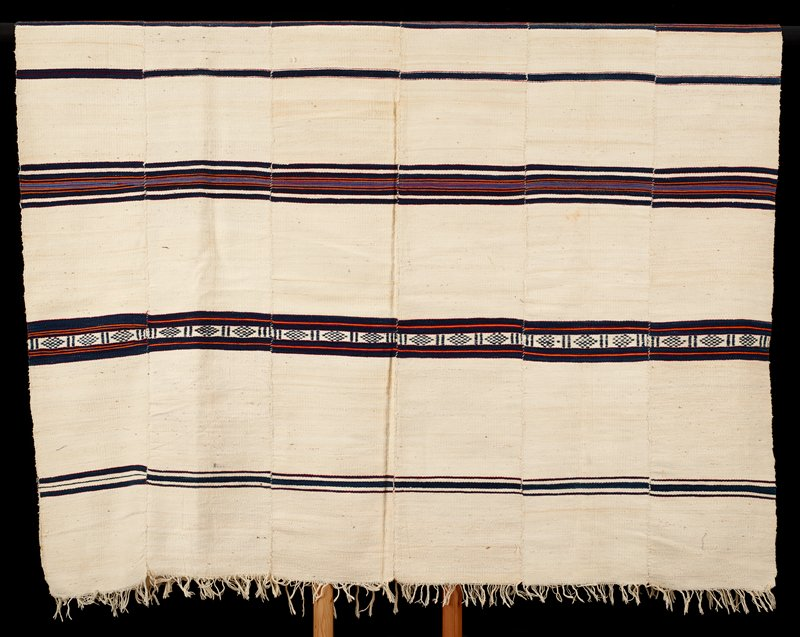 six panels sewn together; cream ground with dark blue stripes with cream patterning and orange, red and lighter blue thin stripes; twisted fringed on short ends