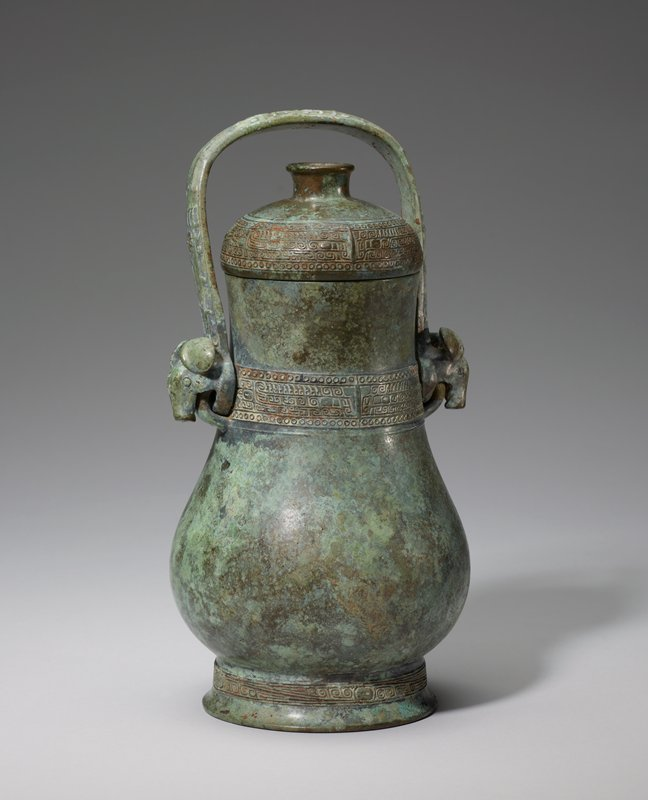 Wine Can, HU (YU)?, inscribed. This vessel type, tall with round cross section, is customarily called 'YU' if it has a handle, 'HU' if it has not. The decor is limited and discreet. The foot belt carries an eyed band with diagonals. The belts on neck and lid, bordered by circle bands, display the animal triple band a highly dissolved bodied t'ao-t'ieh with a row of quills on its back. The flange marking the center line of the face has been reduced to a narrow ridge.The dome-shaped lid has a ring knob and no collar. The handle, adorned with rams' heads at the ends, displays the same kind of cramped t'ao-t'ieh as that on the 'Yu' 50.46.94 - Karlgren plate 21. Patina grey-green.