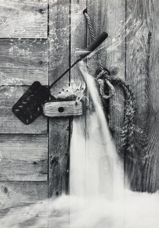 spatula on latch on weathered wooden door with frayed rope pull; milkweed seeds on door latch; white foggy element (smoke) extending down from handle of spatula to bottom of image (double exposure?)