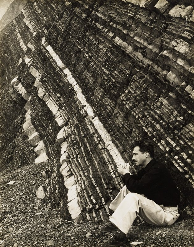 man seated on ground, wearing dark shirt and light pants, in profile from PL; diagonal lines of rock layers on rock formation behind man