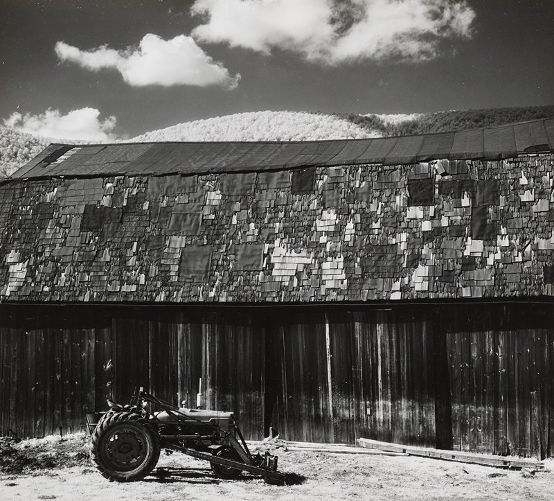 tractor; side of old weathered barn with irregular-patched shingles; tree covered mountain beyond above roof; clouds in sky
