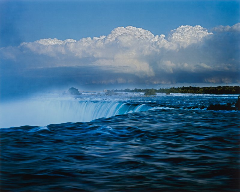 color photograph for blue sky and white clouds over water and a horseshoe shaped waterfall