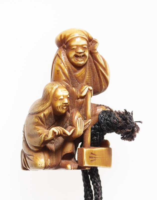 elderly couple: male figure stands leaning on farm tool; female figure crouches, holding object between her hands