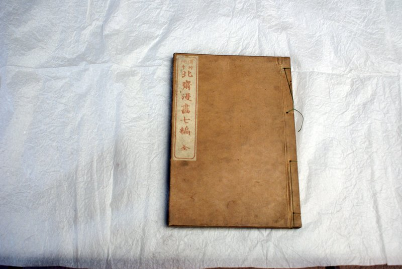 tan bound book of various woodblock printed images: mostly landmarks, nature scenes, and travelers